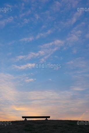 夕映えの丘の上のベンチの写真素材 [FYI02977862]