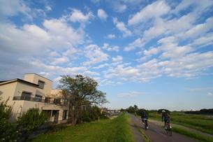 秋雲の下を走る自転車(サイクリング)の写真素材 [FYI02977880]