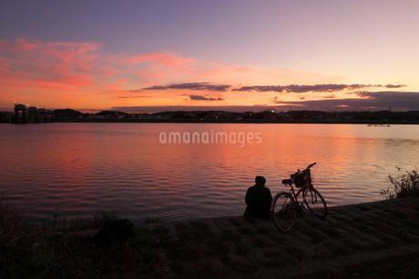 夕映えの川を見つめる人の写真素材 [FYI02977897]