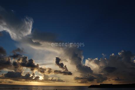 夕焼けでオレンジ色の雲と穏やかな海の写真素材 [FYI02978008]