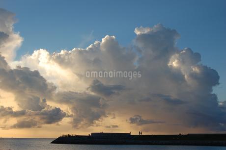 夕焼けでオレンジ色の雲と穏やかな海の写真素材 [FYI02978009]