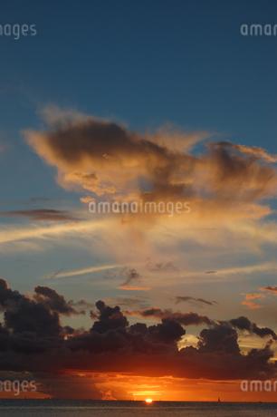 夕焼けでオレンジ色の雲と穏やかな海の写真素材 [FYI02978019]
