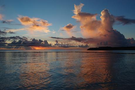 夕焼けでオレンジ色の雲と穏やかな海の写真素材 [FYI02978021]