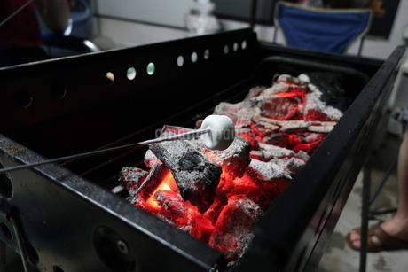 バーベキューコンロの炭火で炙られるマシュマロの写真素材 [FYI02978866]