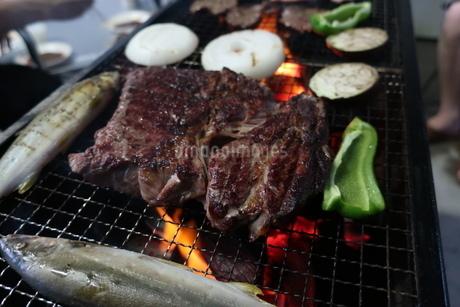 大きな牛肉と魚が乗ったバーベキューコンロの写真素材 [FYI02978872]