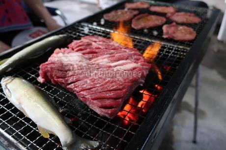 大きな牛肉と魚が乗ったバーベキューコンロの写真素材 [FYI02978873]