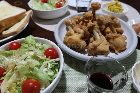 チューリップ唐揚げとサラダの乗った食卓の写真素材 [FYI02978876]