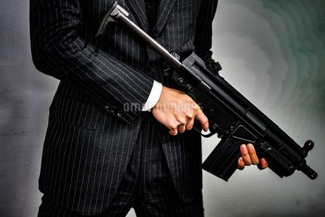 マシンガンを持つ戦うビジネスマンの写真素材 [FYI02978908]