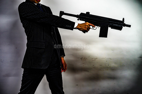 マシンガンを持つ戦うビジネスマンの写真素材 [FYI02978911]
