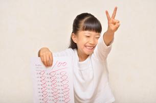 テストで100点を取って喜ぶ女の子の写真素材 [FYI02978935]