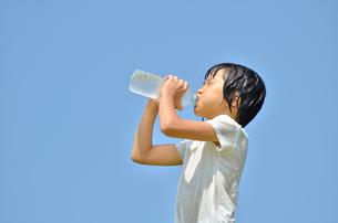 水を飲む小学生の女の子(びしょ濡れ)の写真素材 [FYI02979031]