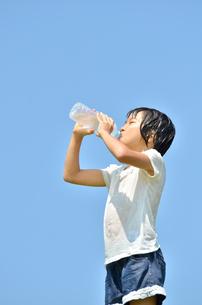 水を飲む小学生の女の子(びしょ濡れ)の写真素材 [FYI02979036]