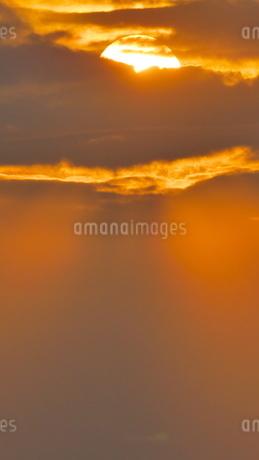 赤い雲の間の夕陽と薄明光線の写真素材 [FYI02979055]