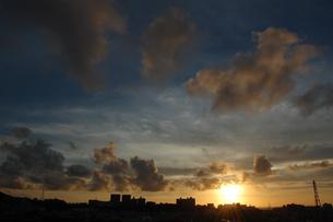 夕焼けで黄金色の空とシルエットの街の写真素材 [FYI02979064]