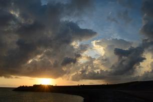 夕暮れの雄大な雲と穏やかな海岸にシルエットの人々の写真素材 [FYI02979298]