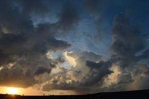 夕暮れの雄大な雲と穏やかな海岸にシルエットの人々の写真素材 [FYI02979306]