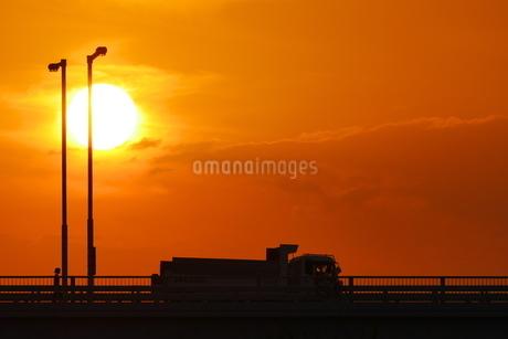 夕陽の中を走るトラックの写真素材 [FYI02979739]