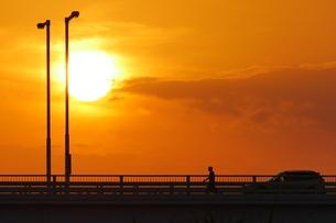夕陽に照らされた橋を渡る人の写真素材 [FYI02979740]