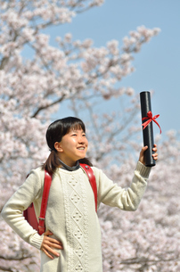 小学生の女の子(桜、ランドセル、卒業証書)の写真素材 [FYI02979845]
