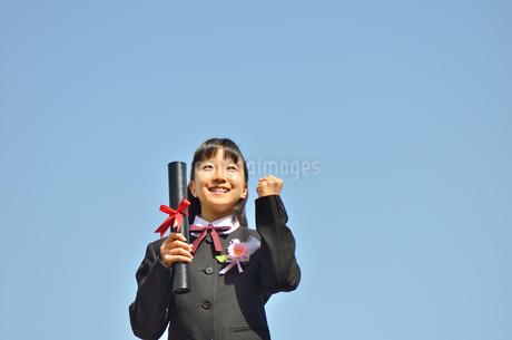青空で笑う小学生の女の子(卒業)の写真素材 [FYI02979868]