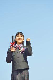 青空で笑う小学生の女の子(卒業)の写真素材 [FYI02979869]