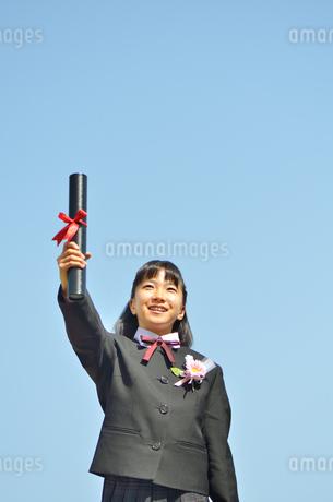 青空で笑う小学生の女の子(卒業)の写真素材 [FYI02979870]