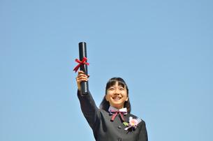青空で笑う小学生の女の子(卒業)の写真素材 [FYI02979872]