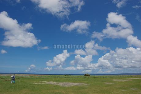 良く晴れた青空とフラットな緑の草原と釣り人の写真素材 [FYI02980638]
