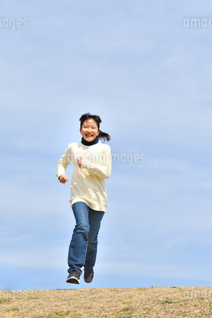 青空で走る女の子(芝生広場)の写真素材 [FYI02980839]