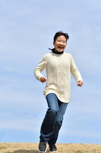 青空で走る女の子(芝生広場)の写真素材 [FYI02980841]