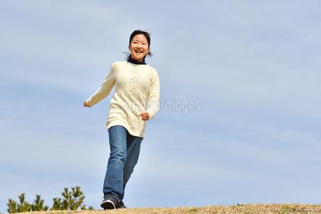 青空で走る女の子(芝生広場)の写真素材 [FYI02980842]