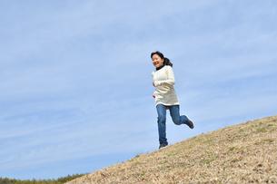 青空で走る女の子(芝生広場)の写真素材 [FYI02980843]