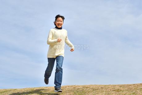 青空で走る女の子(芝生広場)の写真素材 [FYI02980847]