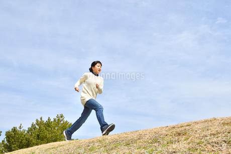 青空で走る女の子(芝生広場)の写真素材 [FYI02980848]