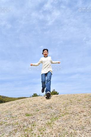 青空で走る女の子(芝生広場)の写真素材 [FYI02980850]