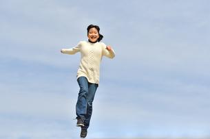 青空でジャンプする女の子の写真素材 [FYI02980857]