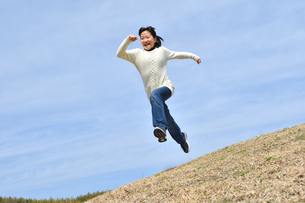 青空でジャンプする女の子(芝生広場)の写真素材 [FYI02980858]
