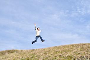 青空でジャンプする女の子(芝生広場)の写真素材 [FYI02980860]