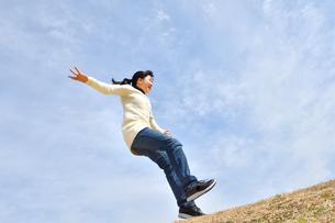 青空でジャンプする女の子(芝生広場)の写真素材 [FYI02980864]