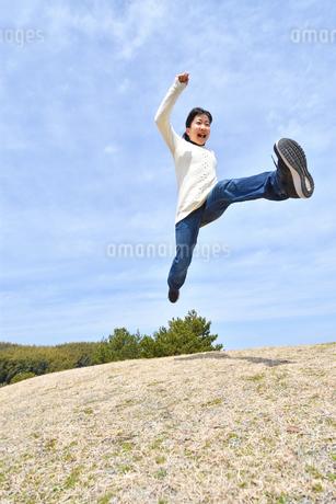 青空でジャンプする女の子(芝生広場)の写真素材 [FYI02980868]