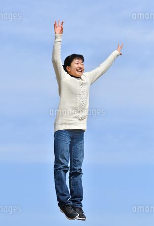 青空でジャンプする女の子の写真素材 [FYI02980873]