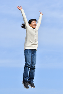 青空でジャンプする女の子の写真素材 [FYI02980874]