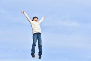 青空でジャンプする女の子の写真素材 [FYI02980878]