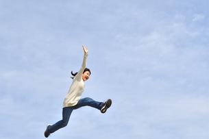 青空でジャンプする女の子の写真素材 [FYI02980881]