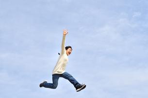 青空でジャンプする女の子の写真素材 [FYI02980883]