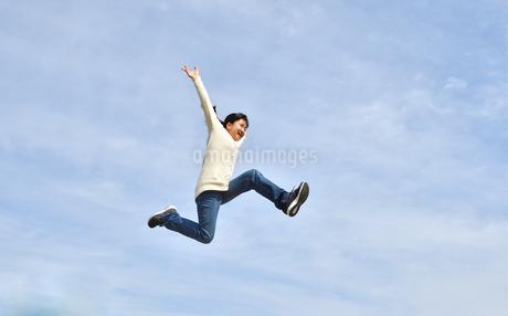 青空でジャンプする女の子の写真素材 [FYI02980885]