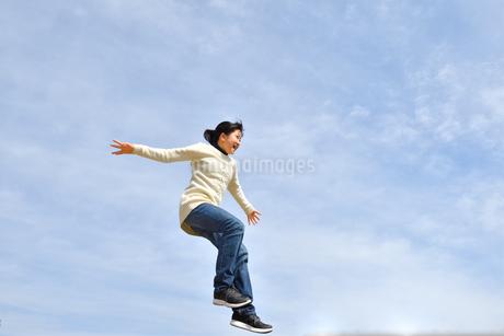 青空でジャンプする女の子の写真素材 [FYI02980888]
