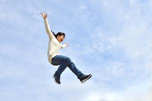 青空でジャンプする女の子の写真素材 [FYI02980895]