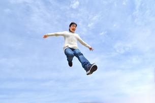 青空でジャンプする女の子の写真素材 [FYI02980896]