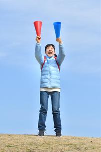 青空で応援する女の子(冬)の写真素材 [FYI02980900]